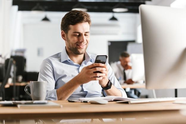 Homme D'affaires Souriant, écrire Un Message Sur Smartphone Alors Qu'il était Assis Près De La Table Au Bureau Photo Premium