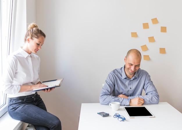 Homme d'affaires souriant en regardant une tablette numérique avec une femme d'affaires en regardant le journal dans le bureau Photo gratuit