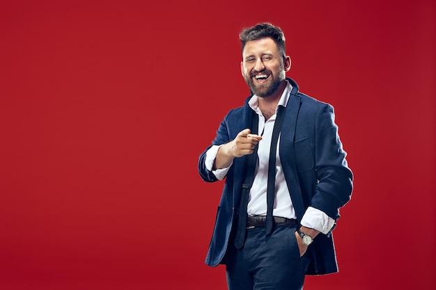 Homme D'affaires Souriant Vous Pointer, Vous Voulez, Portrait Gros Plan Demi-longueur Sur Fond De Studio Rouge. Photo gratuit