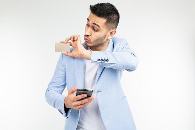Homme D'affaires Surpris Dans Une Veste Bleue Avec Une Carte De Crédit Avec Une Maquette Et Un Smartphone à La Main Sur Un Fond De Studio Blanc Photo Premium