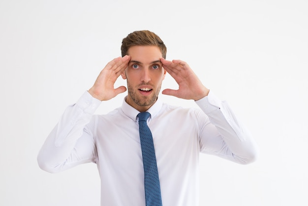 Homme d'affaires surpris touchant les tempes avec la bouche ouverte Photo gratuit