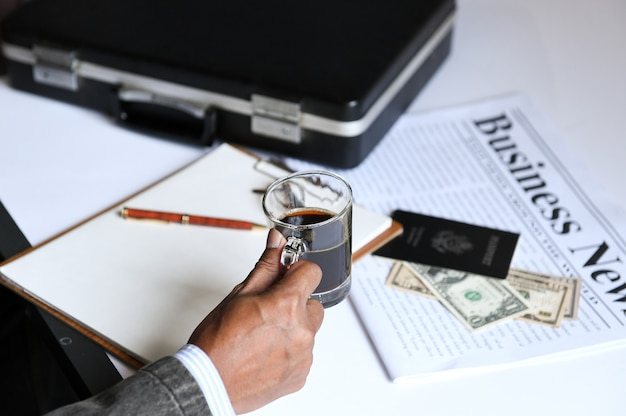 Homme d'affaires tenant un café avec le journal des affaires. Photo Premium