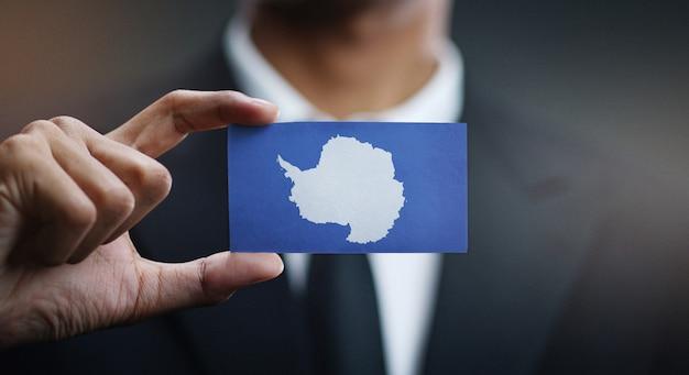 Homme d'affaires tenant une carte du drapeau de l'antarctique Photo Premium