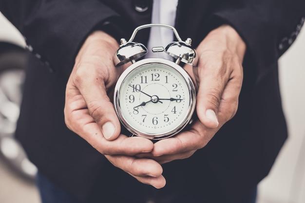 Homme d'affaires tenant l'horloge rétro devant la voiture blanche Photo Premium