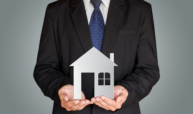 Homme D'affaires Tenant La Maison De Papier Dans Ses Mains, Concept Immobilier Photo Premium