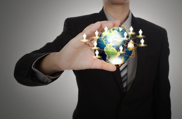 Homme D'affaires Tenant Une Planète Terre Avec Les Gens Symboles Photo gratuit