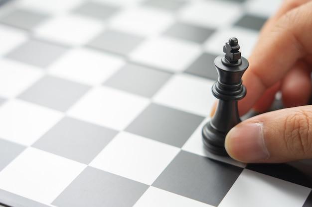 Un homme d'affaires tenant un roi aux échecs est placé sur un échiquier. Photo Premium