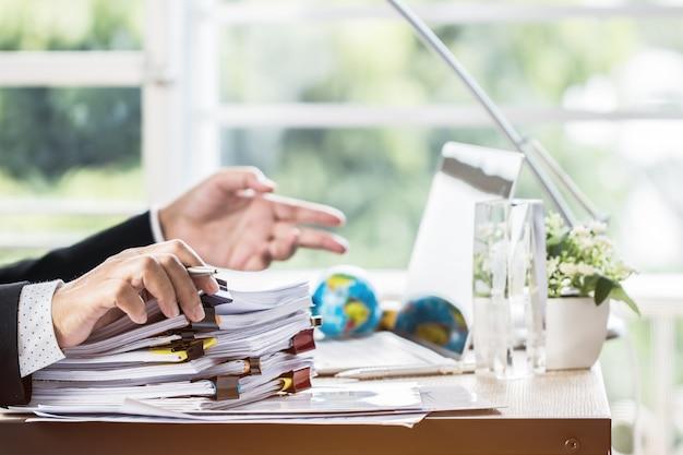 Homme d'affaires tenant un stylo pour travailler dans des piles de fichiers papier à la recherche d'informations Photo Premium