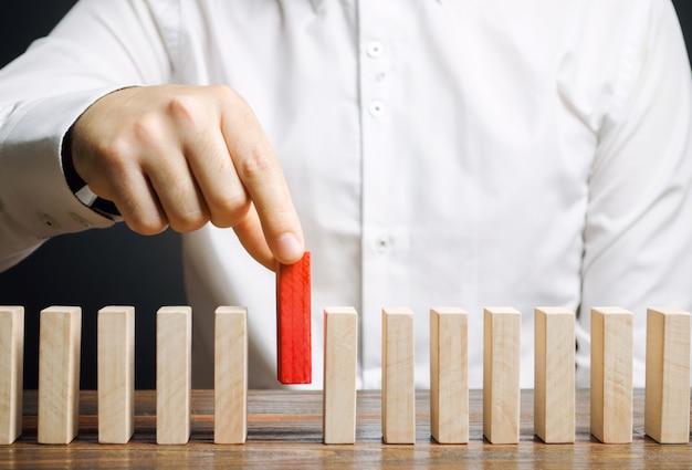 Homme d'affaires tient un bloc de bois dans ses mains. Photo Premium
