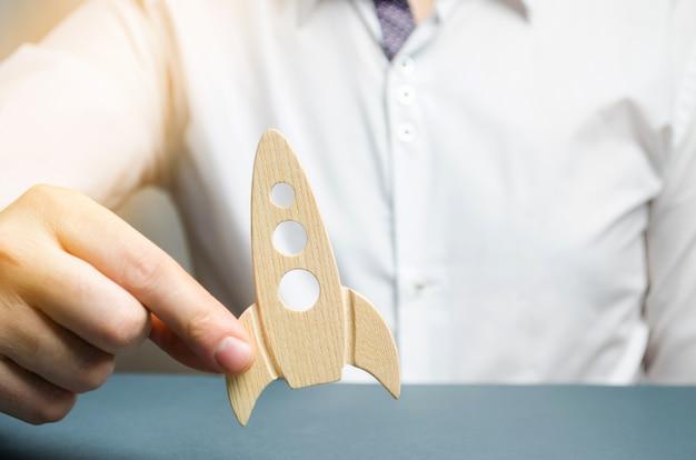 Homme d'affaires tient une fusée en bois dans sa main. le concept de collecte de fonds pour une startup. Photo Premium