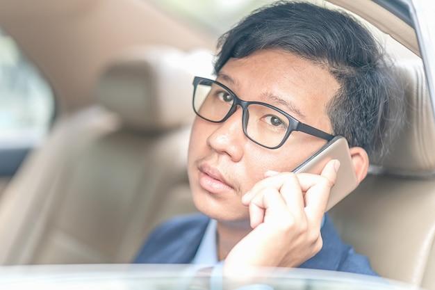 Homme d'affaires travaillant à l'arrière d'une voiture Photo Premium