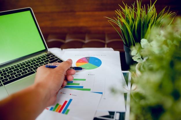 Homme d'affaires travaillant au bureau et graphiques sur son bureau. business concept et espace de copie Photo Premium