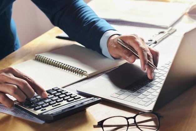 Homme D'affaires Travaillant Sur Le Bureau Avec L'aide De La Calculatrice Et De L'ordinateur Au Bureau. Concept Comptabilité Finance Photo Premium