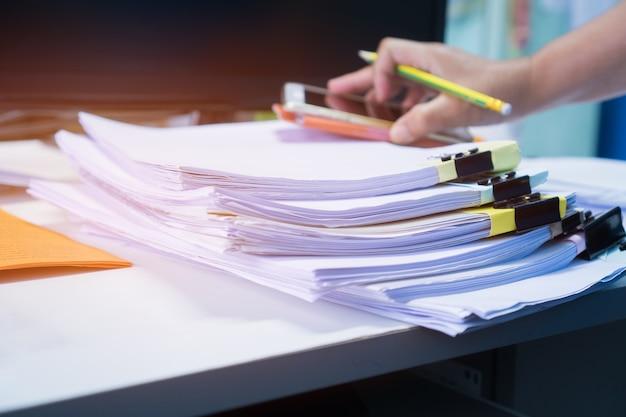 Homme d'affaires travaillant dans des dossiers papier stacks Photo Premium