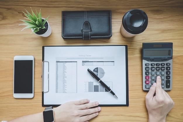 Homme d'affaires travaillant sur un document graphique rapport financier et coût de calcul d'analyse avec calculatrice au bureau Photo Premium