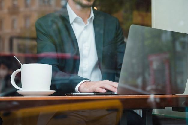 Homme d'affaires travaillant sur un ordinateur portable au café vu à travers le verre Photo gratuit