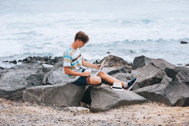 Homme d'affaires travaillant sur la plage avec un ordinateur portable Photo Premium