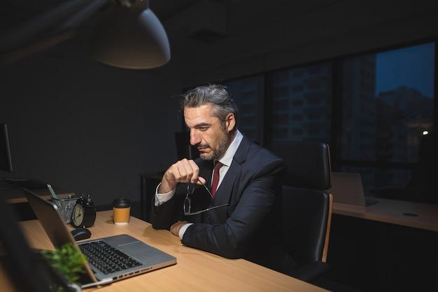 Homme D'affaires Travaillant Tard Assis Sur Le Bureau Au Bureau La Nuit Photo Premium