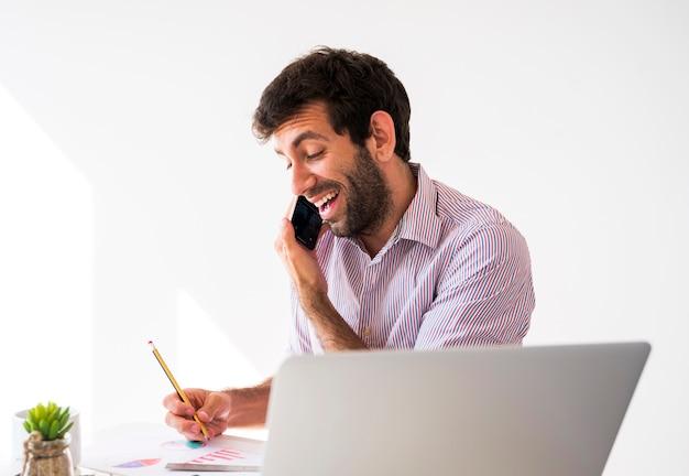 Homme d'affaires travaillant avec un téléphone portable et un ordinateur portable Photo gratuit