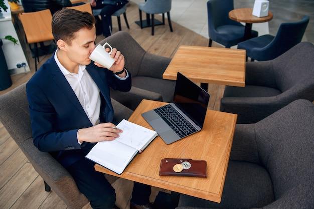 Homme D'affaires Travaille Sur Son Lieu De Travail Avec Ordinateur Portable, Ordinateur Portable Et élabore Un Plan D'affaires Photo Premium
