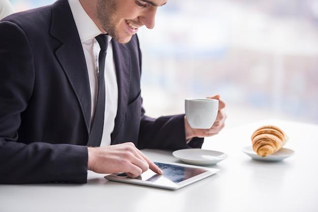 Homme d'affaires travaille avec tablette et boire du café. Photo Premium