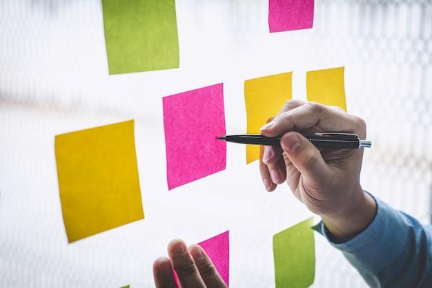Homme d'affaires utiliser post it notes à la planification idée et stratégie de marketing d'entreprise, pense-bête sur le mur de verre Photo Premium