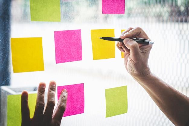 Homme d'affaires utiliser post it notes à la planification idée et stratégie de marketing d'entreprise, pense-bête sur le mur Photo Premium