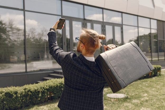 Homme D'affaires Avec Valise Marchant Dans Une Ville D'été Photo gratuit