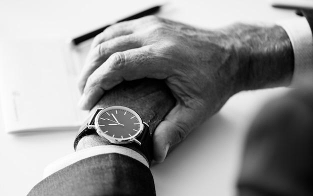 Homme d'affaires vérifiant l'heure à la main montre Photo gratuit