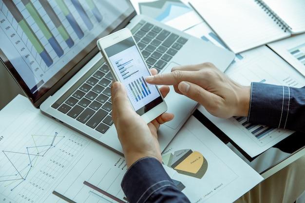 Homme d'affaires vérifie le graphique de données de son entreprise à travers les téléphones mobiles et les ordinateurs portables. Photo Premium