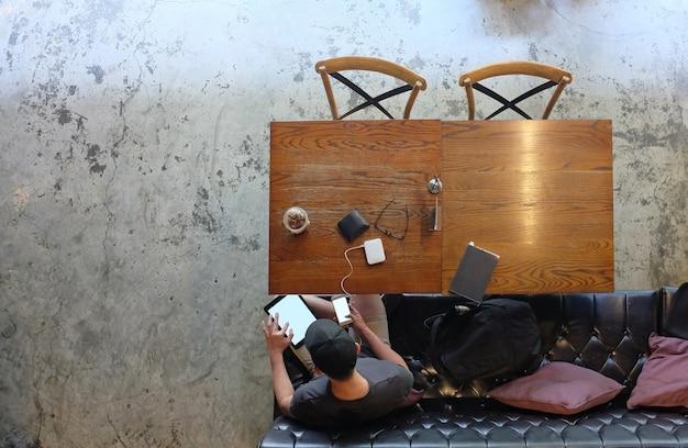 Homme D'affaires En Vêtements Décontractés S'asseoir à La Table Avec Une Tablette Dans Ses Mains Et Utilise Un Smartphone Dans Un Café Dans Ses Mains. Vue De Dessus. Photo Premium