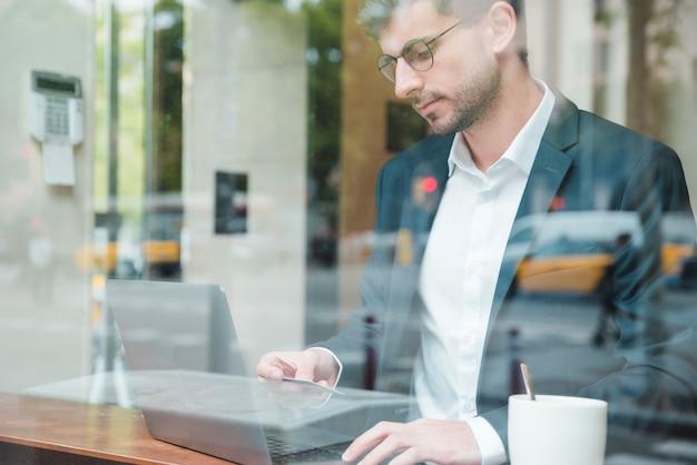 Un homme d'affaires vu à travers le verre en utilisant une carte de crédit pour faire des achats en ligne au café Photo gratuit