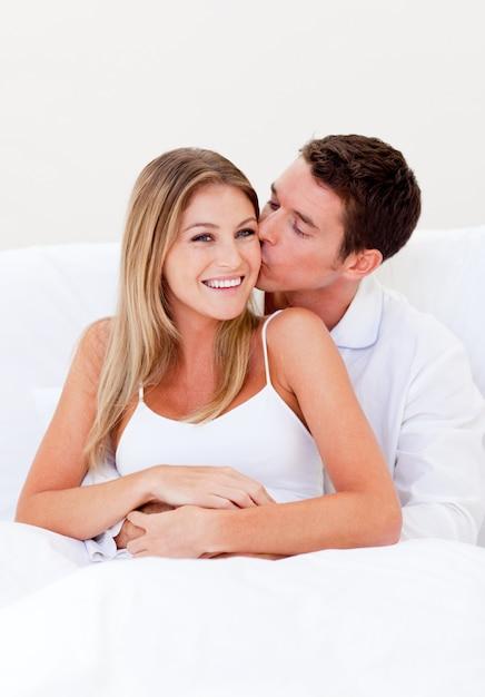 Homme affectueux embrasser sa femme assise sur le lit Photo Premium