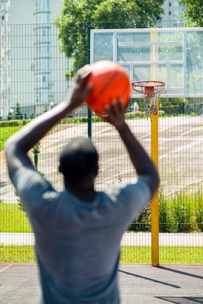 Homme africain, lancer balle, dans, cerceau Photo gratuit