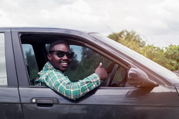 Homme africain portant des lunettes de soleil et souriant assis dans une voiture avec une fenêtre ouverte. Photo Premium
