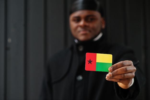 Homme Africain Porter Durag Noir Tenir Le Drapeau De La Guinée-bissau à La Main Mur Sombre Isolé. Photo Premium