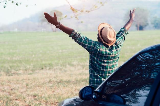 Homme africain voyageur hipster à la recherche et assis sur la voiture Photo Premium