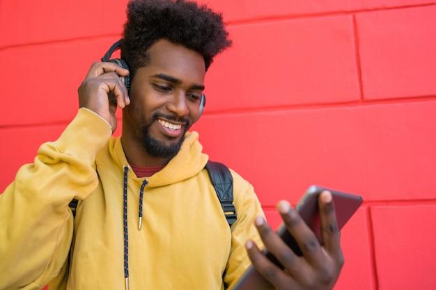 Homme Afro à L'aide De Sa Tablette Numérique Avec Des écouteurs. Photo gratuit