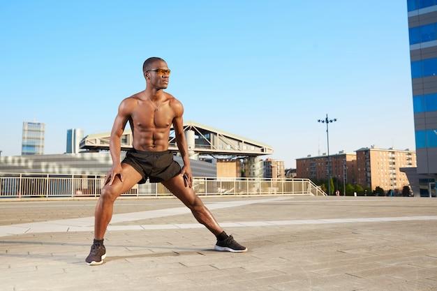 Homme afro-américain faisant des étirements en milieu urbain Photo Premium