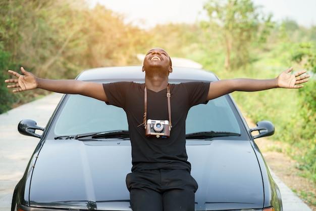 Homme afro-américain de liberté debout avec la voiture. Photo Premium