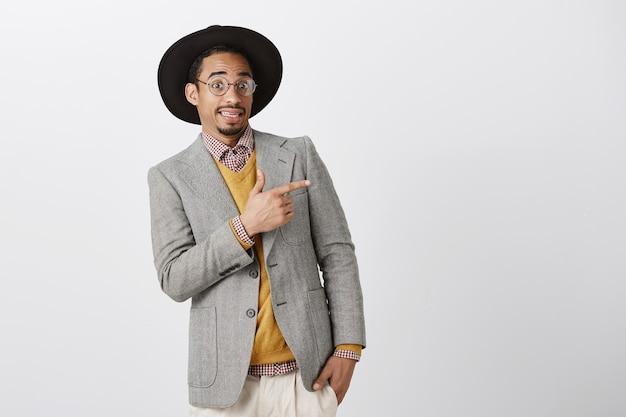 Un Homme Afro-américain Maladroit Et Mécontent S'incline Et Grince Des Dents, Pointant Le Coin Supérieur Droit Quelque Chose D'effrayant Photo gratuit