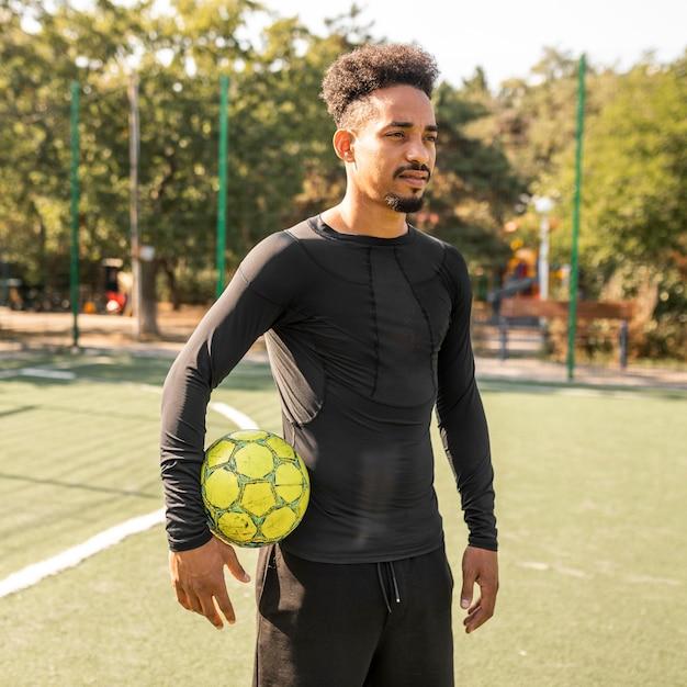 Homme Afro-américain Posant Avec Un Ballon De Football Sur Un Terrain Photo Premium
