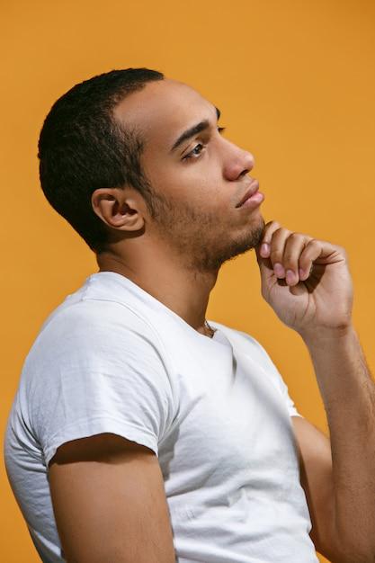 Homme Afro-américain Réfléchi Regarde Pensivement Contre L'orange Photo gratuit