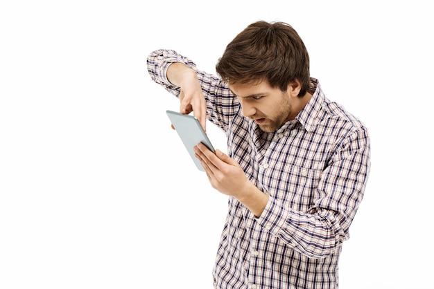 Homme Agacé Appuyez Sur Une Tablette Numérique Photo gratuit