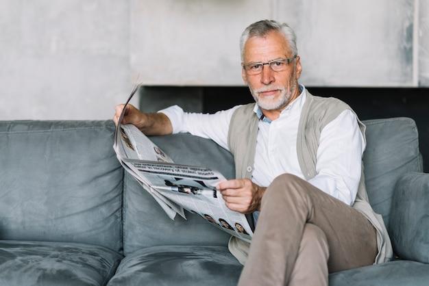 Un homme âgé assis sur un canapé en lisant un journal Photo gratuit