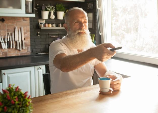 Homme âgé Barbu Regardant La Télévision Avec Télécommande Photo Premium