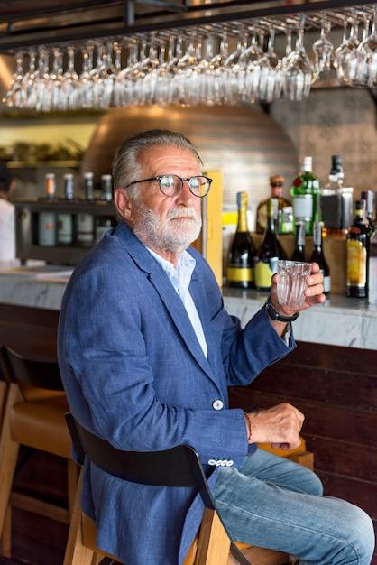 Un homme âgé est assis dans un pub Photo Premium