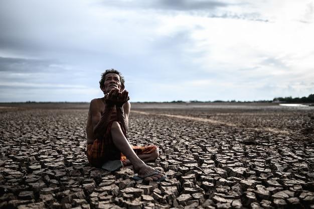 Un homme âgé était assis, demandant de la pluie pendant la saison sèche et le réchauffement climatique Photo gratuit