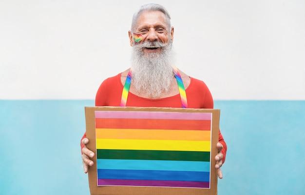 Homme âgé à La Fierté Gay Tenant La Bannière Lgbt Arc-en-ciel Photo Premium