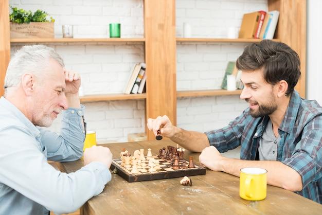 Homme âgé et jeune homme jouant aux échecs à table dans la chambre Photo gratuit